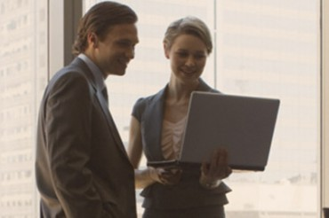 Man and women looking at laptop together in office